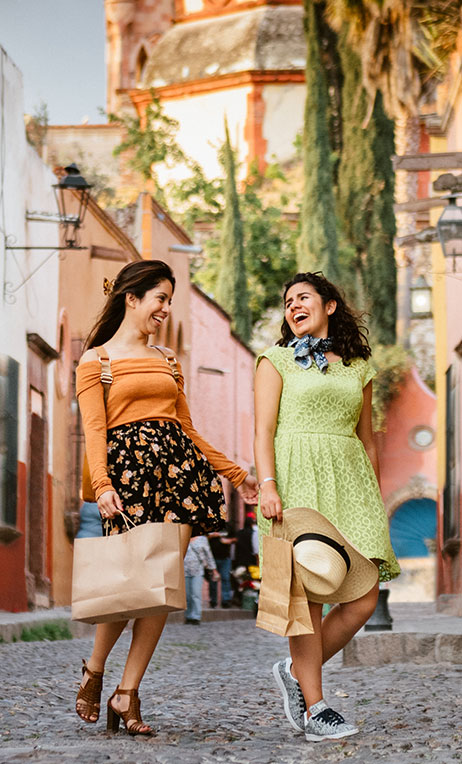 Mexico – Two young women laughing and carrying shopping bags in Mexico.