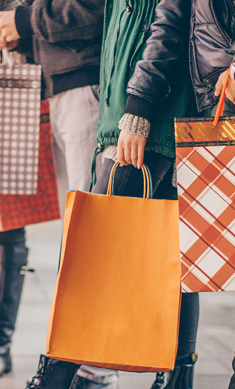 DACH – Group of consumers holding holiday inspired shopping bags.