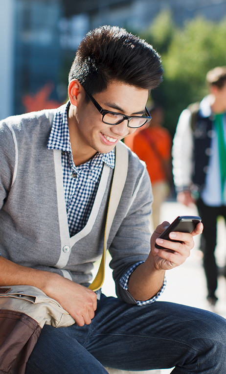 Wireless – Smiling student using his cell phone.