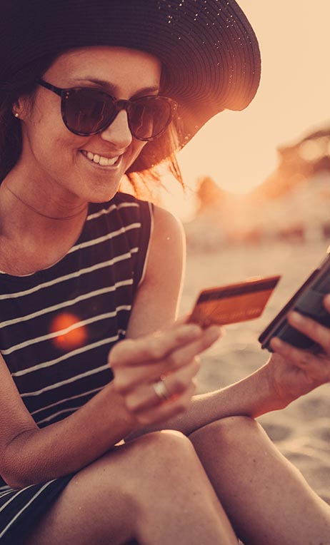Financial Services – Woman at the beach using her prepaid credit card online.