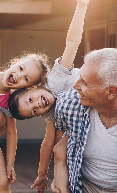 Healthcare Incentives and Rewards – Grandfather playing with his grandchildren.