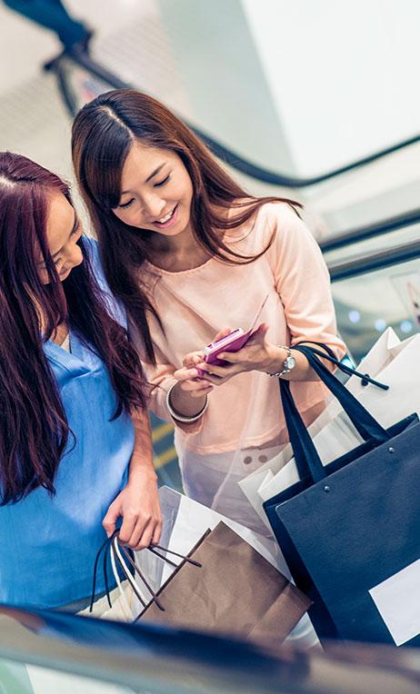 Hong Kong – Two teenagers carrying shopping bags on a mall escalator.
