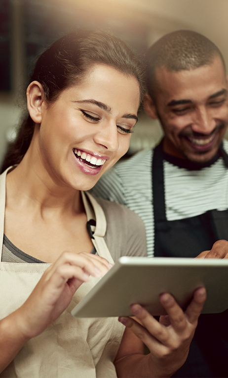 In–Store – Two business owners smiling and looking at a tablet device.