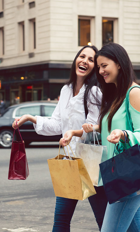 North America – Two smiling women walking with shopping bags.