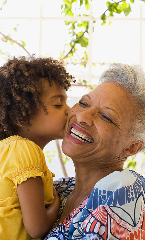 Healthcare Incentives – Granddaughter kissing her grandmother.