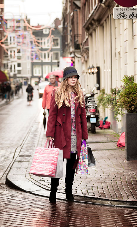 Netherlands and Belgium – Young woman shopping during the holidays in Amsterdam.