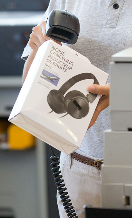 Returns – Cashier scanning noise-cancelling headphones product at cash register.