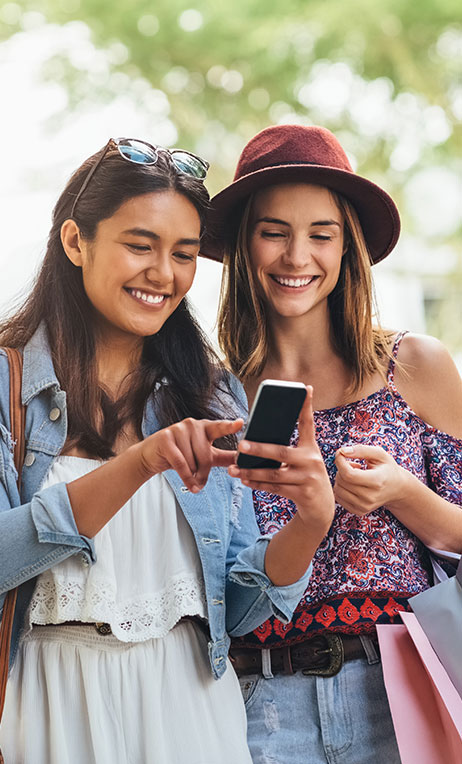 InComm – Image of two young women smiling and looking at a mobile device.