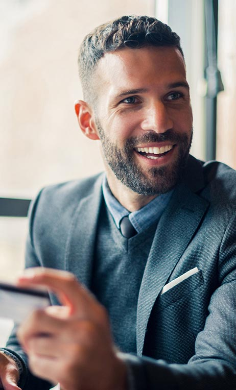 Partners – Businessman smiling with a prepaid credit card in hand.