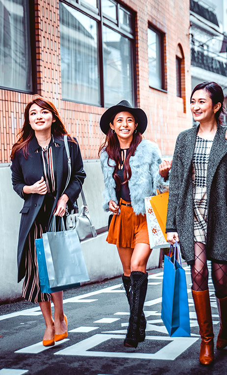 North Asia – Young women walking with shopping bags in Japan.