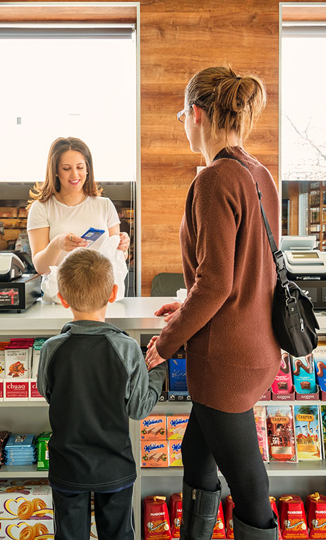 Canada – Woman buying groceries from a convenience store.