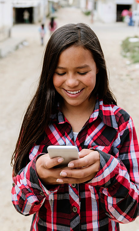 Colombia – Preteen girl looking at online content on her cell phone.