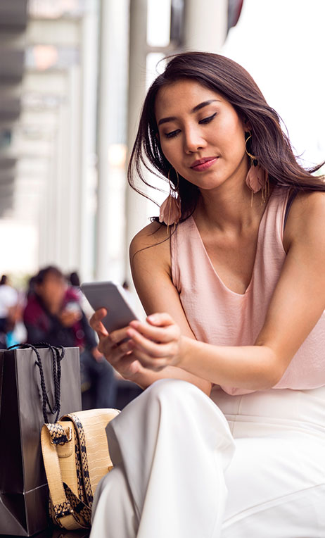 Thailand – Young woman looking at online conent on her phone.