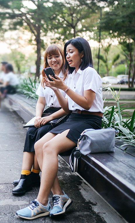 South East Asia – Teens looking at digital content on a mobile phone.