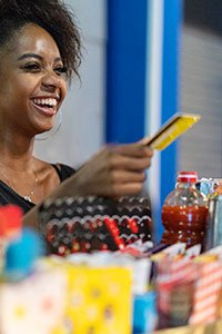 Brazil – Young woman paying for products with a prepaid credit card.