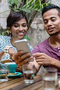 Malaysia – Young man and woman looking at mobile device.