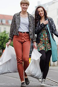 Germany– Two young women carrying large shopping bags in Germany.