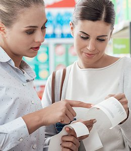 Fintech Insights – Two customers reviewing a receipt at the grocery store.