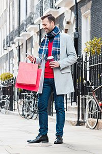 UK – Man carrying shopping bags and looking at his mobile phone.