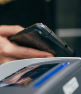 Fintech Insights – Customer holding their cell phone next to a cash register.