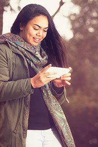New Zealand – Woman looking at digital content on her cell phone.