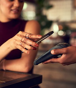 Fintech Insights – Customer holding mobile phone over a point–of–sale device to digitally pay cashier.