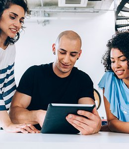 Fintech Insights – Group of millennials looking at a tablet device.