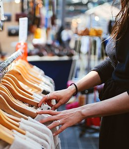 Fintech Insights – Woman browsing a selection of shirts in a clothing store.