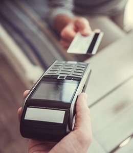 Fintech Insights – Customer ready to slide gift card into point-of-sale device.