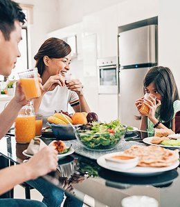 Fintech Insights – Image of a family eating a health lunch at a kitchen table.