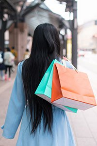 Japan – View of a woman from behind carrying shopping bags over her shoulder.