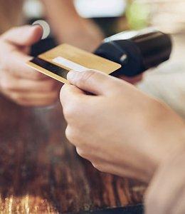 Fintech Insights – Customer handing cashier their gift card.