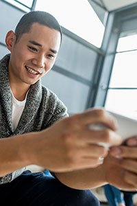Taiwan – Young man playing a video game on his mobile device.