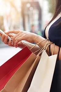 China – Close–up of woman holding a mobile device and three shopping bags.