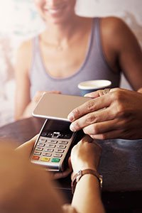 Australia – Customer using a mobile phone to digitally pay at point of sale.