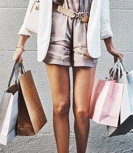 Fintech Insights – Stylish woman carrying five retail shopping bags.
