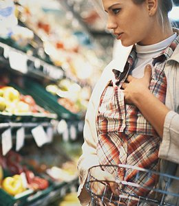 Fintech Insights – Woman shopping in the produce section of a grocery store.