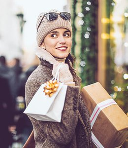 Fintech Insights – Woman holding holiday–decorated present and shopping bag.
