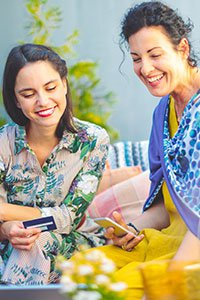 Puerto Rico – Mother and daughter using a prepaid card and mobile phone to shop online.