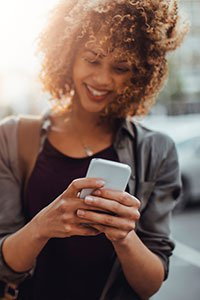 Incentives – Woman looking at digital gift card on mobile phone.