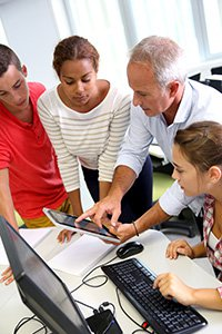 InComm Internships – Image of a business man pointing showing a tablet device to three young people.