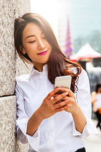 South Korea – Young woman looking at her cell phone in South Korea.