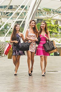 Singapore – Group of young women carrying shopping bags.